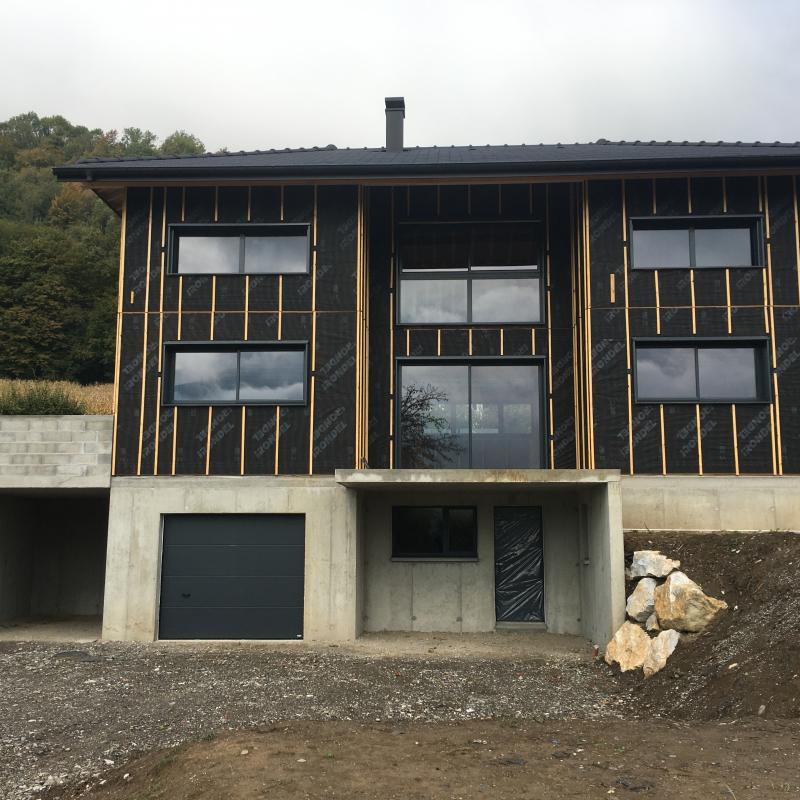 Maison ossature bois en cours de construction, terrain en pente, en Savoie